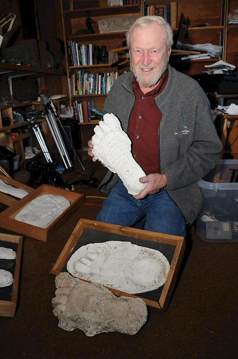 John Bindernagel shown with casts of Sasquatch footprints.