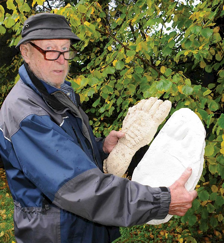 John Bidernagel holding casts of Sasquatch footprints.
